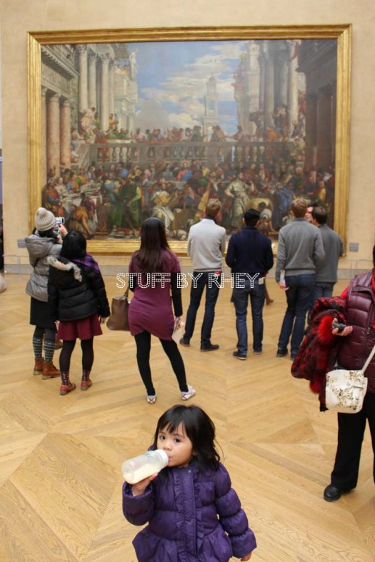 Aria at the grand gallery infront of the Mona Lisa, the big painting of the Wedding at Cana behind her