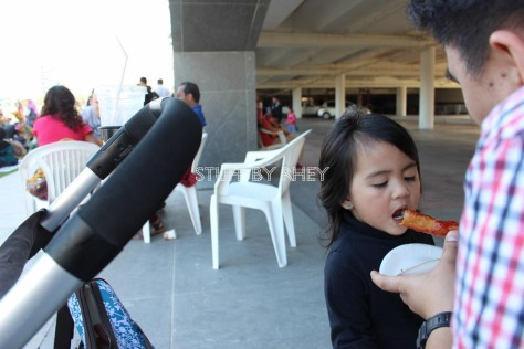 Eating corn dog at the MIA Park Bazaar